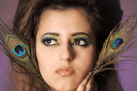 Portarit of beautiful young girl with peacock feather Stock Photo - 13281013