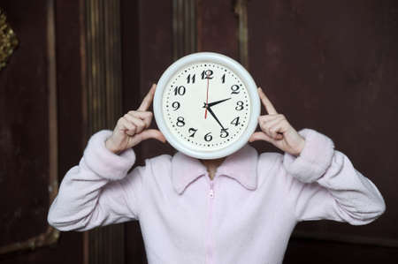 past midnight: Young girl holding a clock  Stock Photo