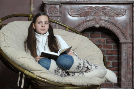 teen girl reads a book while sitting in a chair photo