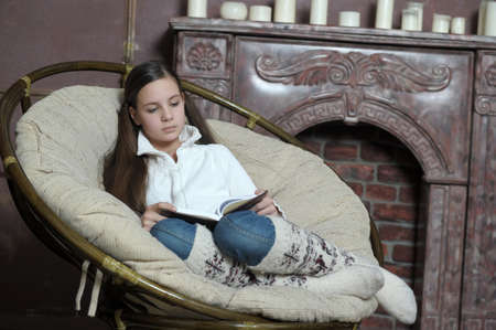 teen girl reads a book while sitting in a chair Stock Photo - 12160911