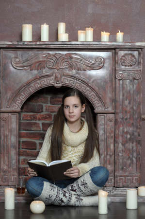 teen girl with a book by the fireplace and candles photo
