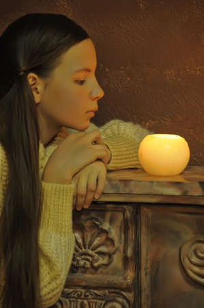 Teen girl looking at a candle photo