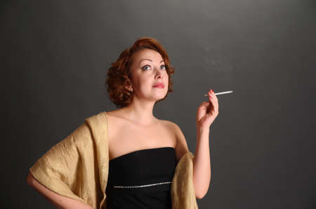 woman with a cigarette on a dark background photo