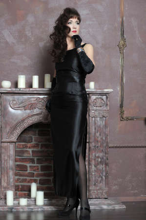 young woman in black elegant dress by the fireplace photo