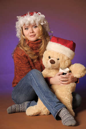 the blonde in a Christmas cap with a toy bear Stock Photo - 13236097