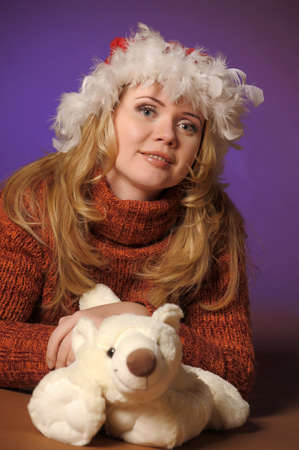 the blonde in a Christmas cap with a toy bear photo