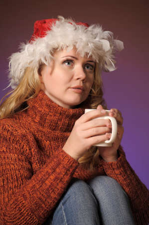 Young woman with santa hat holding a cup Stock Photo - 13236093