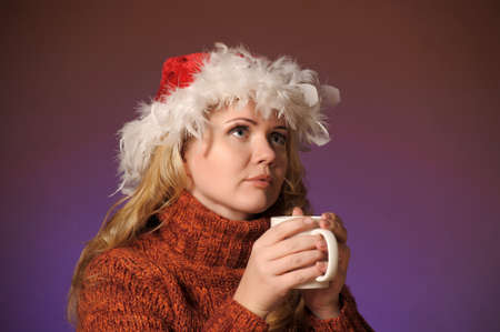 Young woman with santa hat holding a cup photo