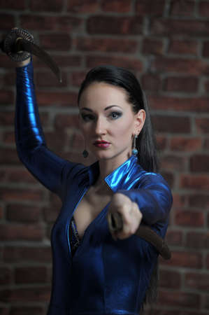 girl in a blue suit with a fitting close katana in hands Stock Photo - 12205024