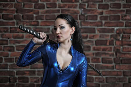 girl in a blue suit with a fitting close katana in hands Stock Photo - 12205030