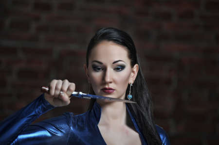 The woman in a suit from latex with a knife in a hand Stock Photo - 12378252