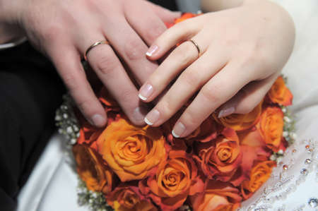 hands of newlyweds at the wedding bouquet of orange roses photo