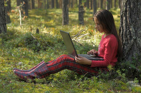 work boots: girl with laptop in the woods Stock Photo