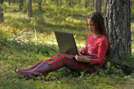 girl with laptop in the woods Stock Photo - 12234114