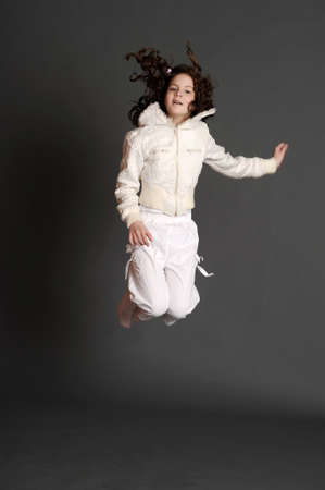 girl jumping in studio on dark background photo