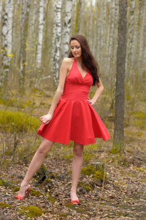 brunette in a red dress in the park photo