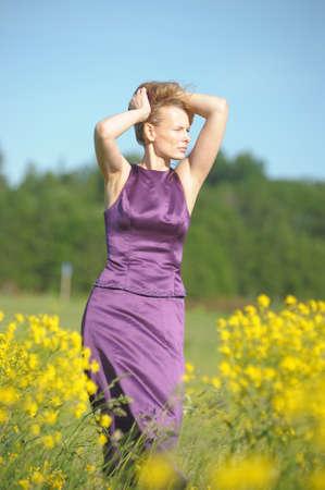 jonge vrouw in een veld van gele bloemen