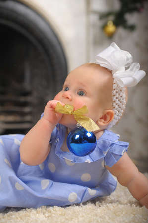Pretty little girl playing with blue ornament balls photo