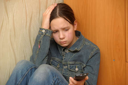 The upset girl with a mobile phone Stock Photo - 13342367
