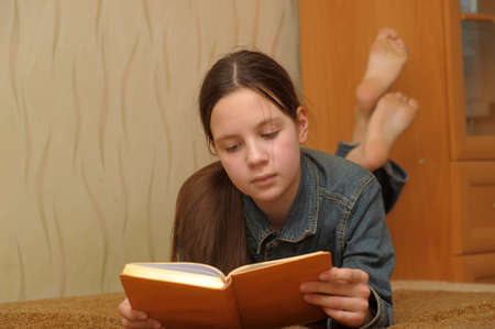 The girl the teenager reads the book lying on a sofa photo