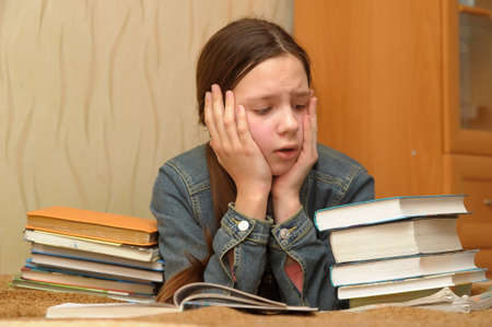 The girl the teenager is upset by the big homework Stock Photo - 12387114
