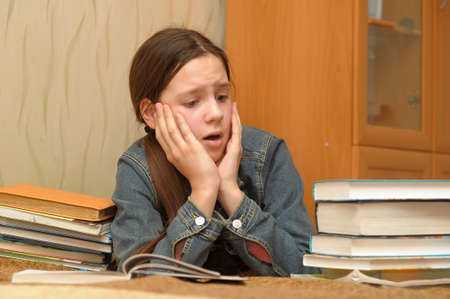 The girl the teenager is upset by the big homework Stock Photo - 12387125