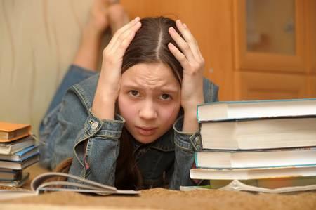 Het meisje van de tiener wordt verstoord door de grote huiswerk Stockfoto