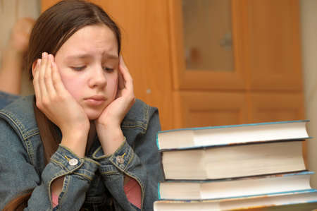 La chica de la adolescente se siente mal por la gran tarea Foto de archivo