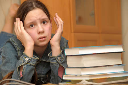 The girl the teenager is upset by the big homework Stock Photo - 12387122