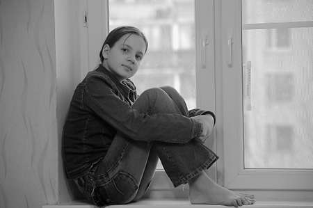 The sad girl the teenager at home on a window sill Stock Photo - 12443056