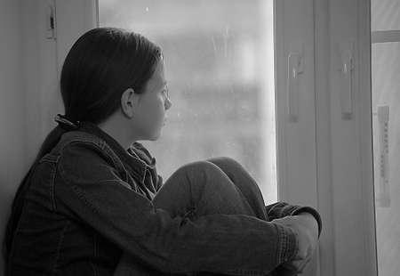 femme triste: La fille triste de l'adolescent � la maison sur un rebord de fen�tre