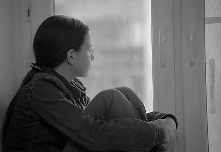 The sad girl the teenager at home on a window sill Stock Photo - 12443058