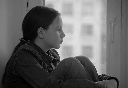 ni�os pobres: La chica triste que el adolescente en su casa en un alf�izar de la ventana