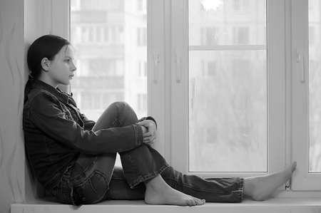ansiedad: La chica triste que el adolescente en su casa en un alf�izar de la ventana