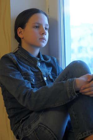 fille triste: La fille triste de l'adolescent à la maison sur un rebord de fenêtre