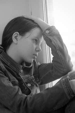 femme inqui�te: La fille triste de l'adolescent � la maison sur un rebord de la fen�tre