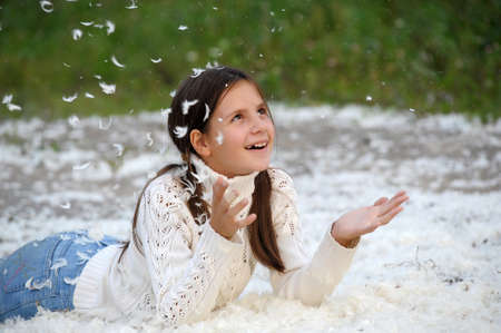 Young beautiful girl filled up by small feathers  Stock Photo - 12986808