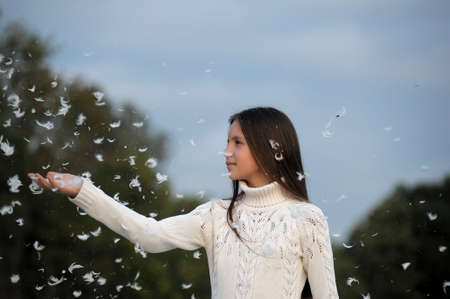 Young beautiful girl filled up by small feathers