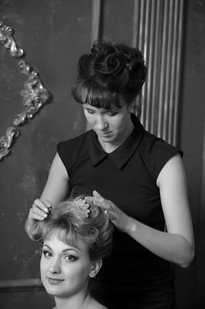 Hairdresser makes hairstyle for young pretty women Stock Photo - 21065361