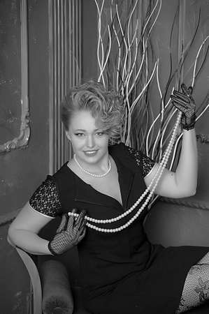 retro photo woman with a black dress with pearl necklace in hand photo