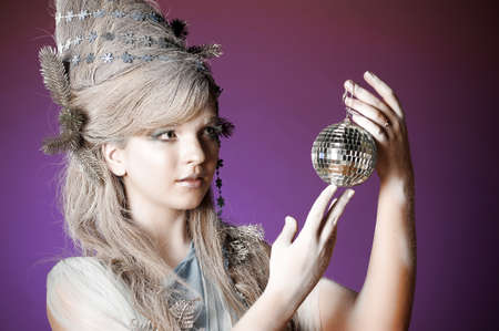woman hanging toy: portrait of a girl with a mirror ball in his hands