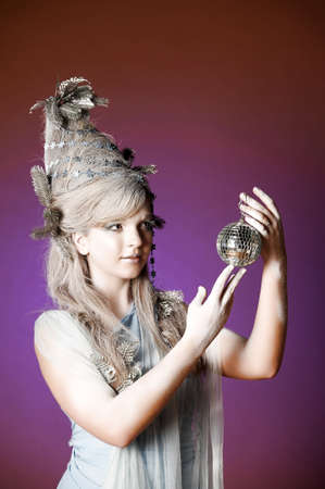 portrait of a girl with a mirror ball in his hands photo