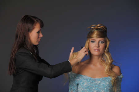 the stylist corrects models a hairdress in studio before shooting Stock Photo - 13295001