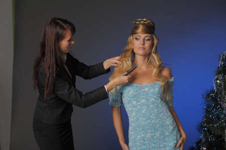 the stylist corrects models a hairdress in studio before shooting photo