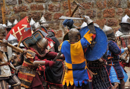 Fight between the pedestrian knights in a heavy armor in a medieval castle against a stone wall ,  Vyborg,Russia, july-31