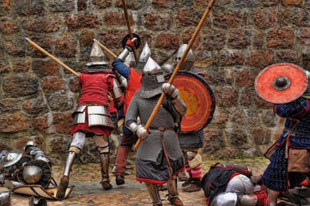 mediaeval: Fight between the pedestrian knights in a heavy armor in a medieval castle against a stone wall ,  Vyborg,Russia, july-31
