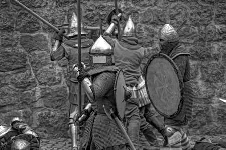 real renaissance: Fight between the pedestrian knights in a heavy armor in a medieval castle against a stone wall ,  Vyborg,Russia, july-31