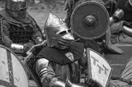 squire: Fight between the pedestrian knights in a heavy armor in a medieval castle against a stone wall ,  Vyborg,Russia, july-31