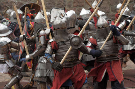 historical battle: Fight between the pedestrian knights in a heavy armor in a medieval castle against a stone wall ,  Vyborg,Russia, july-31