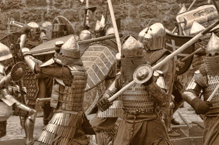 espadas medievales: Lucha entre los caballeros de peatones en una armadura pesada en un castillo medieval contra un muro de piedra, Vyborg, Rusia, julio-31